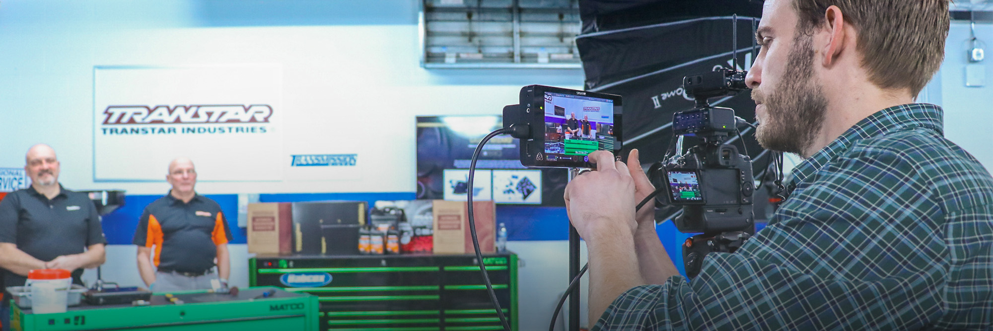 A cameraman filming an autoparts video in Babcox Garage Studio.