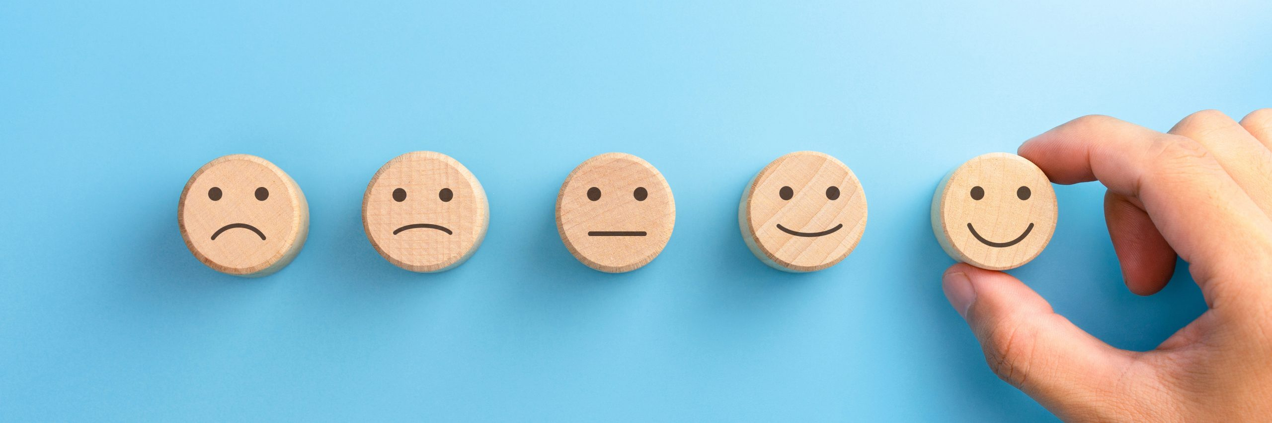 A row of wooden knobs with smiley faces depicting the range of audience experience.