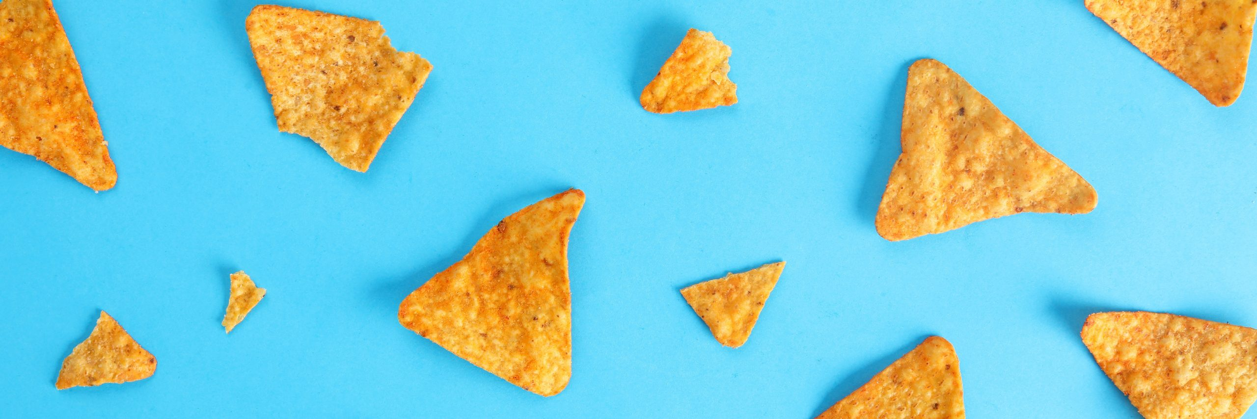 Doritos scattered on a blue surface.