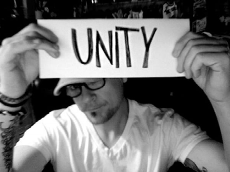 Joe Kalinowski holding up a paper that says Unity.