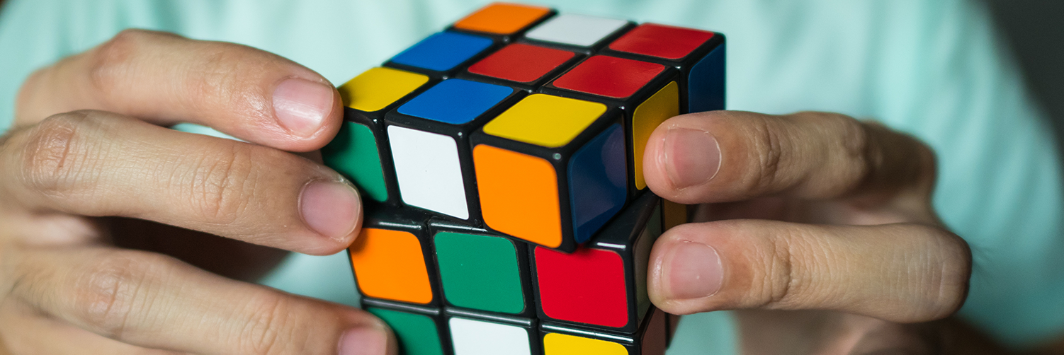 Two hands twisting a Rubik's Cube.
